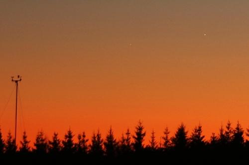 Jupiter ja Merkuur 1. jaanuaril 2009: Pilt on tehtud umbes tund peale päikeseloojangut, kui planeedid olid paari kraadi kõrgusel horisondi kohal. Jupiter on paremal ülal ja heledam, Merkuur keskel ülal ning vaevumärgatav. Tõnis Eenmäe foto.